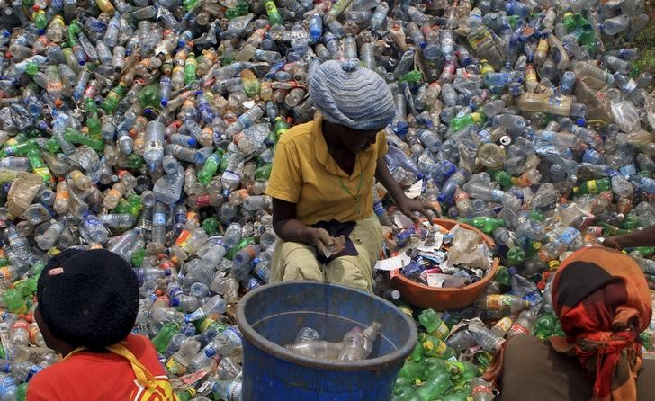 An employee of a recycling plant sorts through plastic bottles at their factory at a dumping site on the outskirts of Uganda's capital Kampala